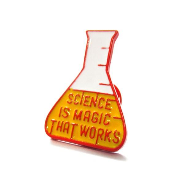 beaker shaped enamel pin that says science is magic