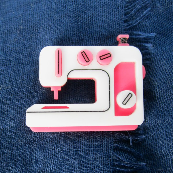 pink sewing machine brooch on blue fabric
