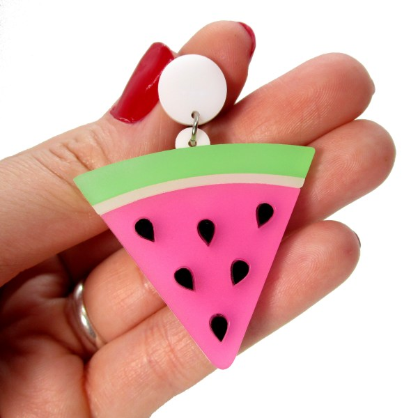hand holding watermelon slice earring to show size