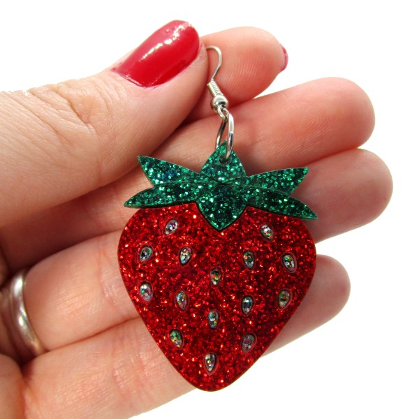 hand holding large glitter red strawberry shape earring to show size
