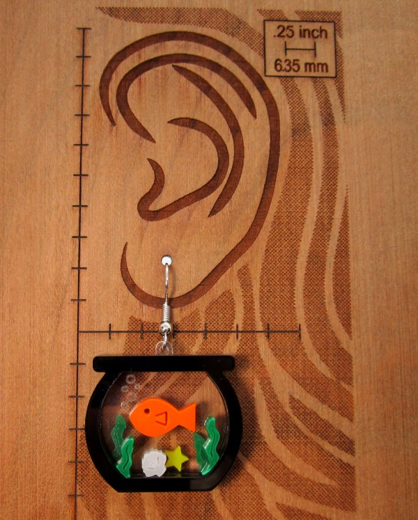 one fish in tank scene earring on board with ear and measurements to show size