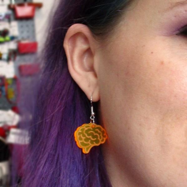 purple hair lady wearing prange brain dangle earring for example