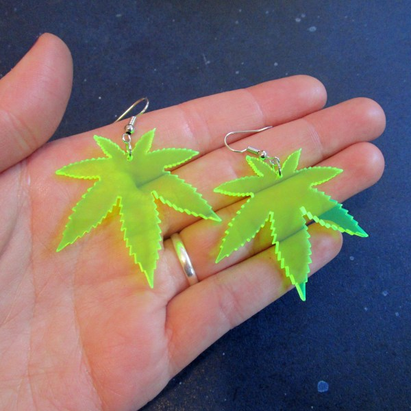 hand holding 2 green pot leaves rave earrings jewelry to show size