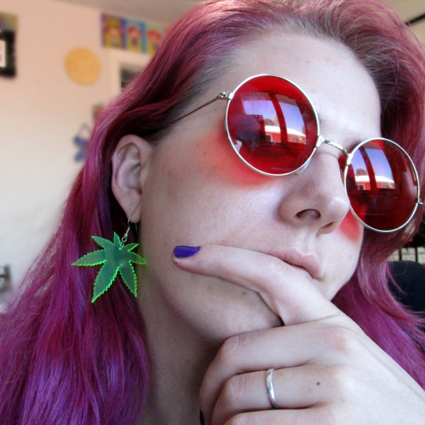 woman in red glasses wearing green pot leaf big neon earrings