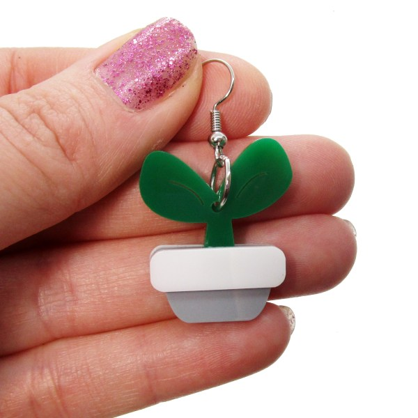 hand holding plastic potted plant dangle earrings to show size