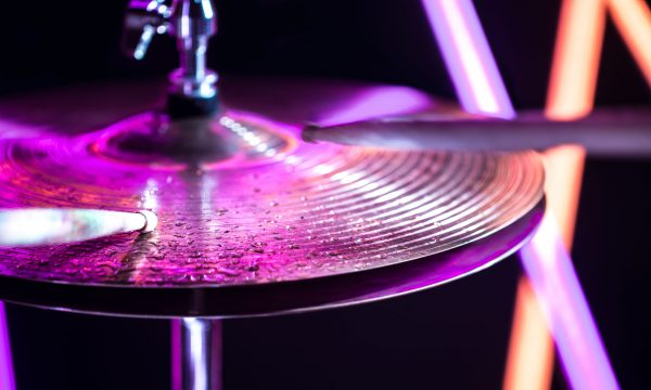 Hi-hat close-up of plates with drumsticks on a background of colored lanterns. Water drops on plates. Musical concept with a working drum.