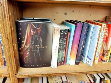 Classroom library shelf showing a face out of the book Dread Nation by Justina Ireland