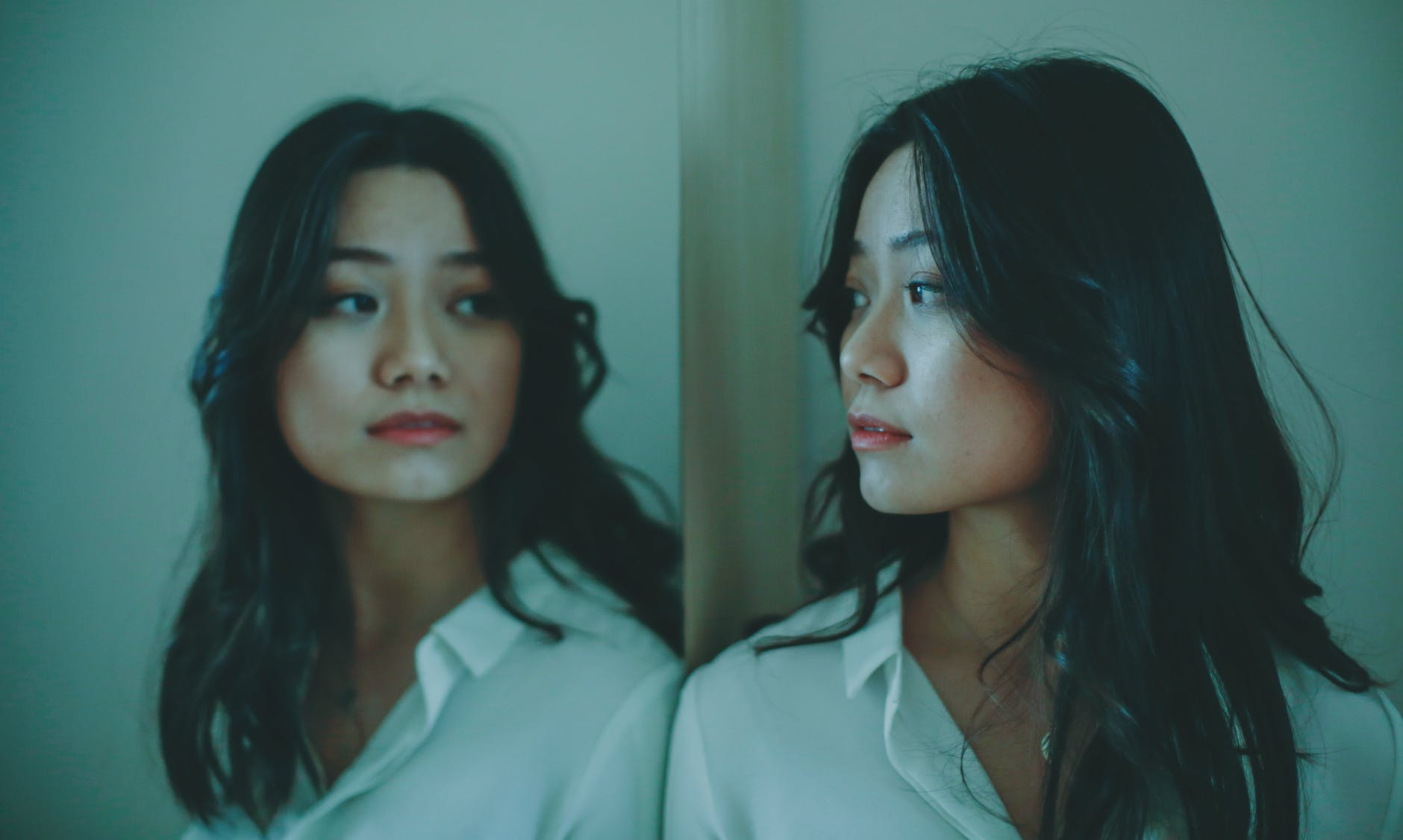 young asian female looking at reflection