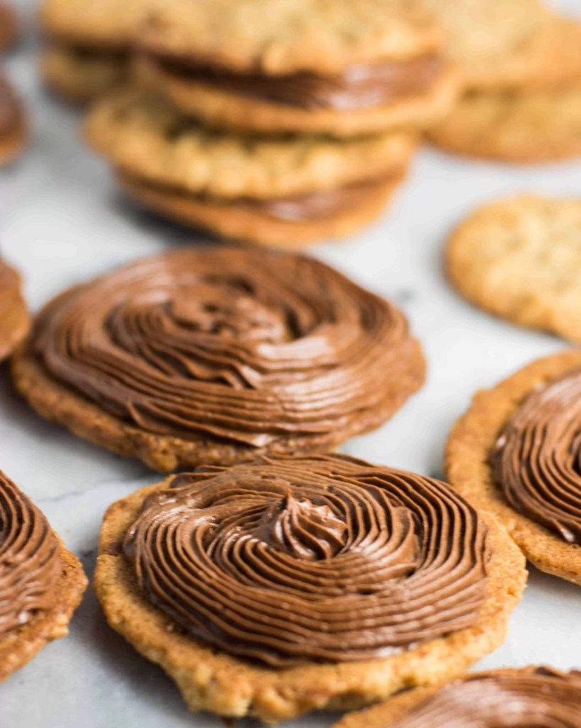 photo of chocolate filling piped onto cookies to be made into chocolate peanut butter sandwich cookies