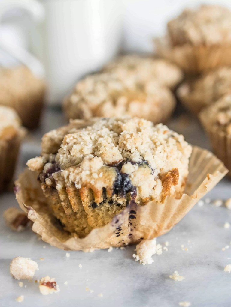 muffin with the wrapper slightly unpeeled with more brown butter blueberry crumb muffins in the background