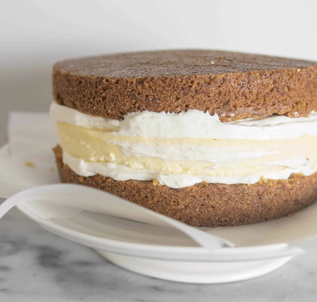 unfrosted carrot cake cheesecake cake sitting on a cake stand