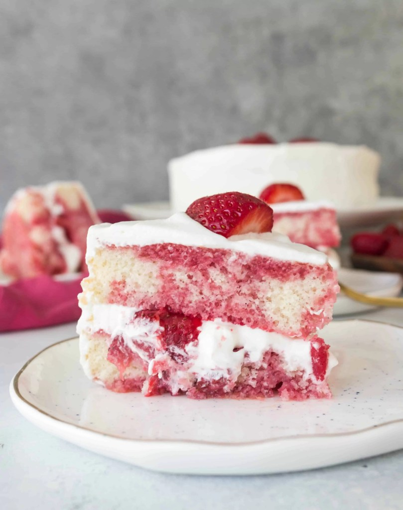 slice of strawberry shortcake layer cake on a plate with the rest of the cake in the background