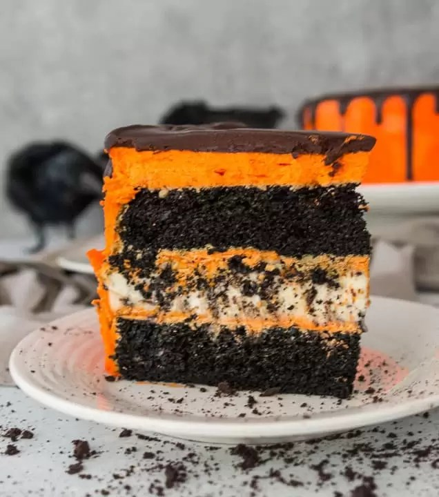 slice of black velvet cookies and cream cheesecake cake on a plate with crushed Oreos scattered around it