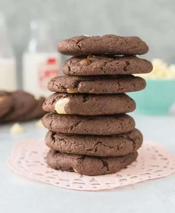 tall stack of 5-ingredient double chocolate caramel cookies sitting on a pink doily