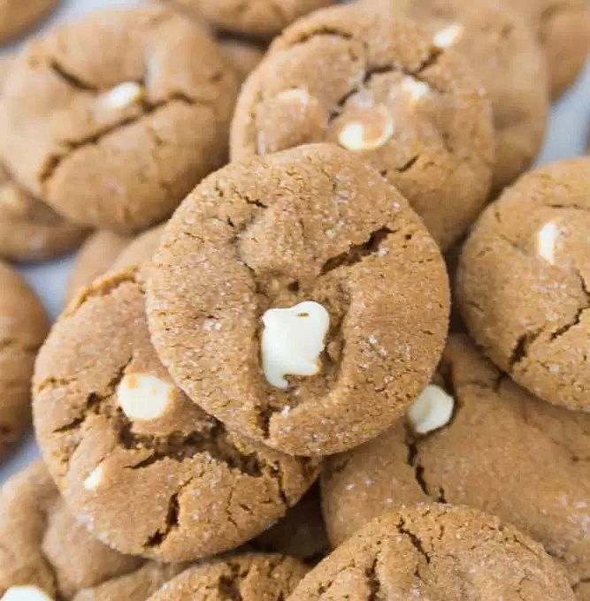 stack of white chocolate molasses cookies with a bottle of milk and more cookies in the background