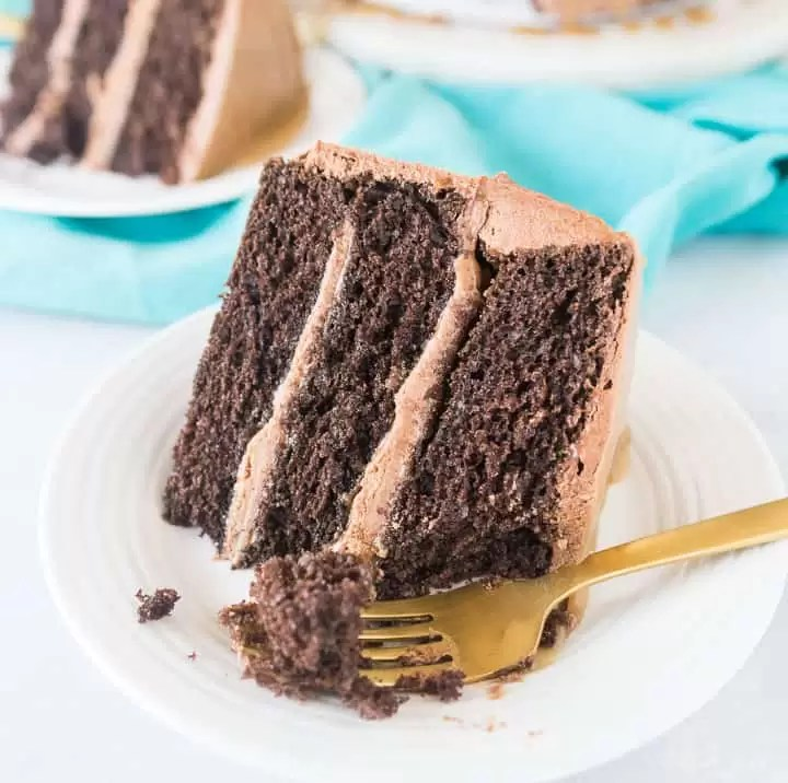 image of a slice of chocolate caramel cake (Milky Way cake) sitting on a plate with a fork taking a piece out
