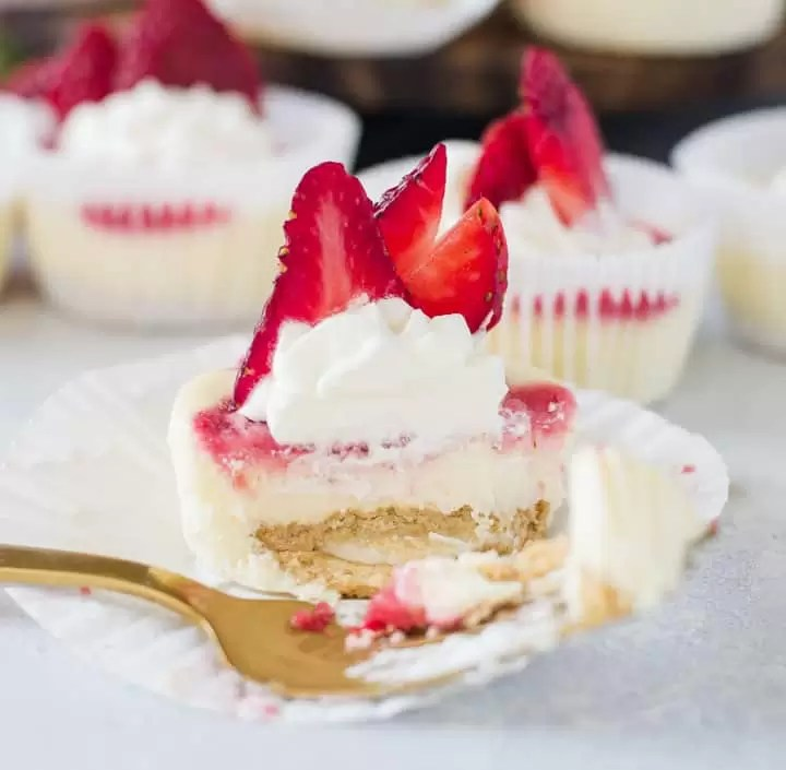 one of the strawberry cheesecake cupcakes with a fork taking a bite out of it