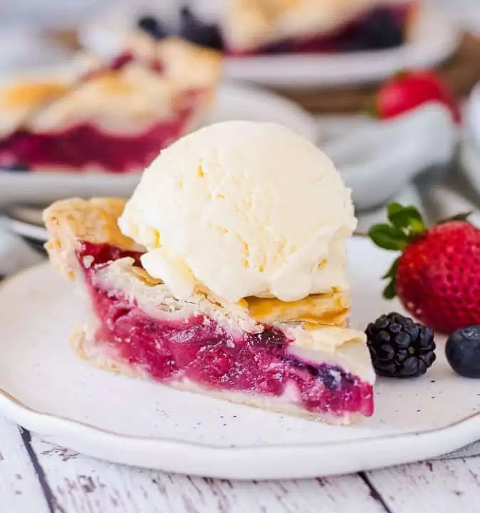 slice of bumbleberry pie on a plate with a scoop of ice cream on top and berries next to it