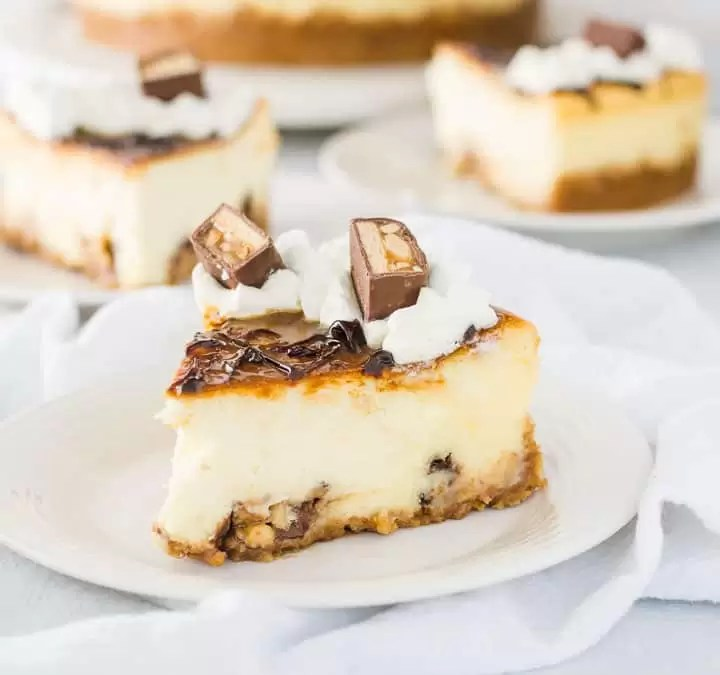 slice of white chocolate snickers cheesecake on a plate with the rest of the cheesecake in the background