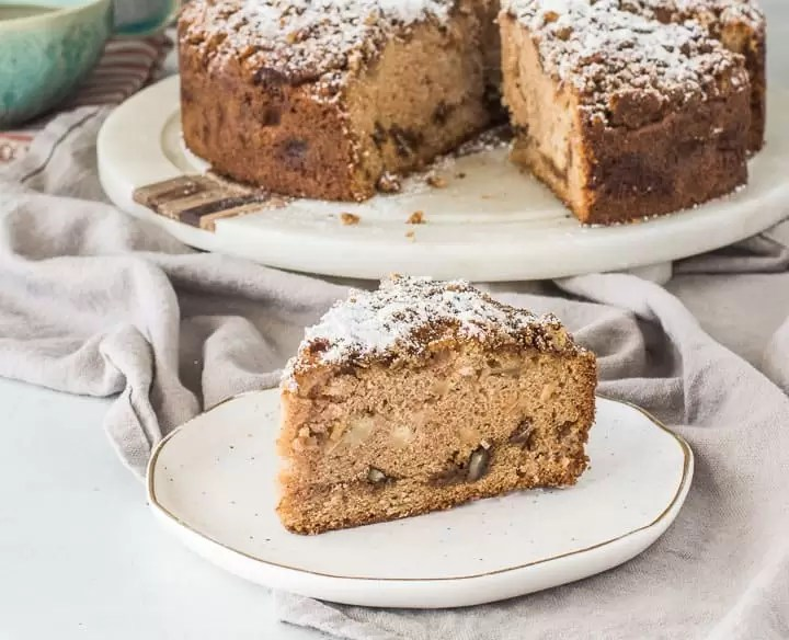slice of apple coffee cake on a plate with the rest of the cake in the background