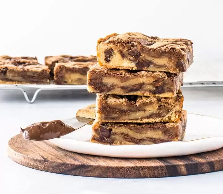 stack of Nutella bars on a plate with more Nutella bars on a wire rack in the background