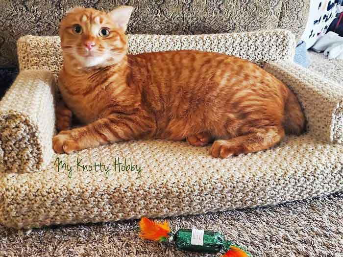 an orange tabby cat with a missing ear lays on a cream colored crochet cat couch