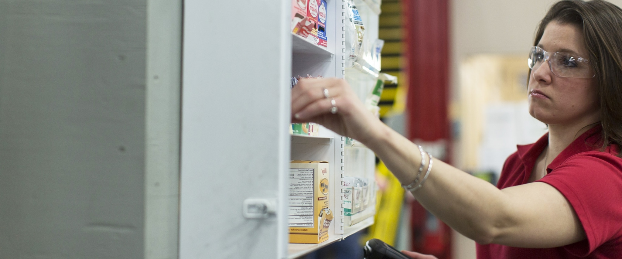 first aid representative restocking a workplace first aid cabinet