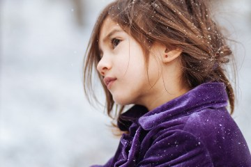 Girl in purple sweater in the snow