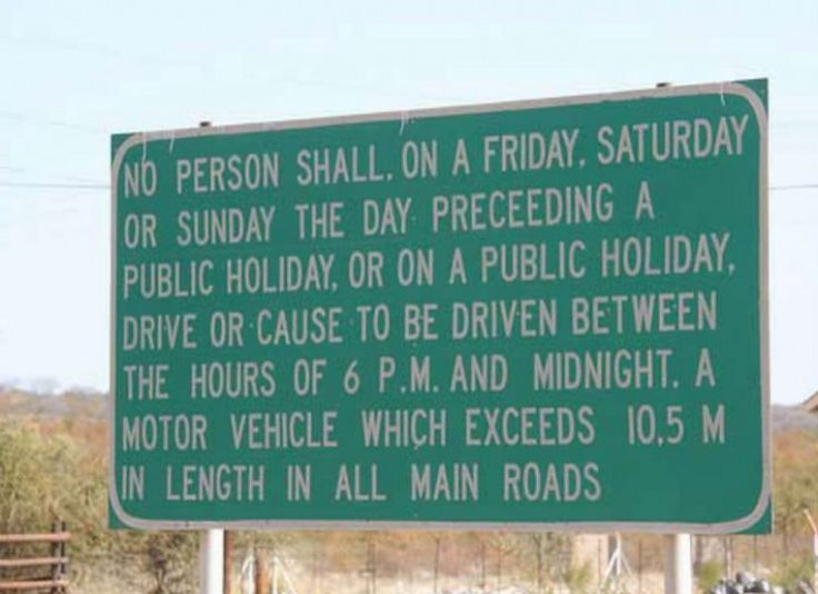 """Road sign that says """"No person shall, on a Friday, Saturday or Sunday the day preceding a public holiday, or on a public holiday, drive or cause to be driven between the hours of 6 P.M. and midnight. A motor vehicle which exceeds 10.5 m in length in all main roads."""""""