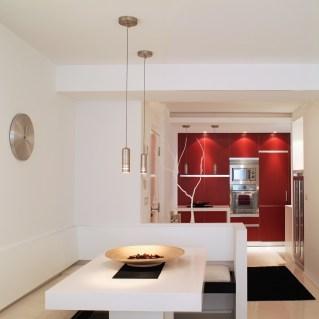 Diseño interior de piso en Galicia. Mesa comedor y bancos con cocina al fondo