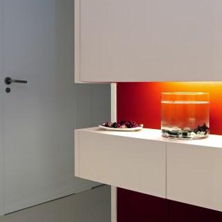 Diseño interior de piso en Galicia. Espacio decorativo con cajones, pintado en el rojo utilizado en toda la vivienda
