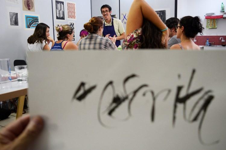 """Participantes da oficina com papel em primeiro plano onde se lê """"A escrita"""""""