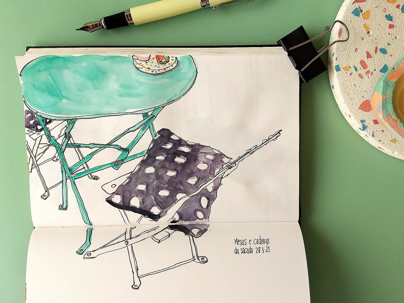 Caderno com desenho de uma mesa redonda com duas cadeiras, todas de metal. O caderno está rodeado por uma caneta e um suporte