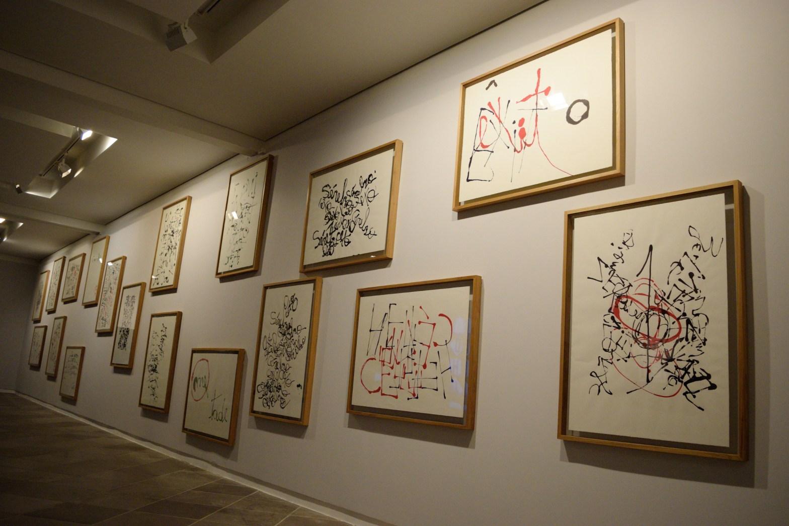 Foto de parede da exposição com quadros da série de caligrafias