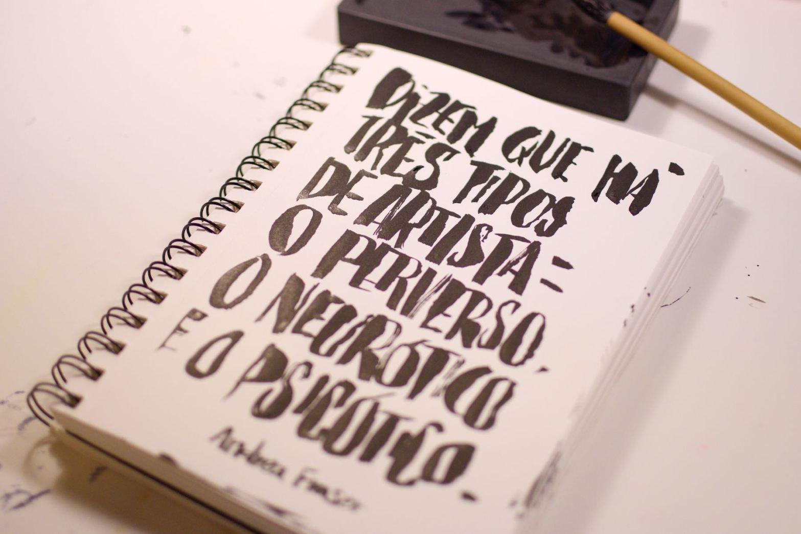 caderno aberto com frase escrita em caligrafia. Vê-se também um pincel apoiado em um suzuri
