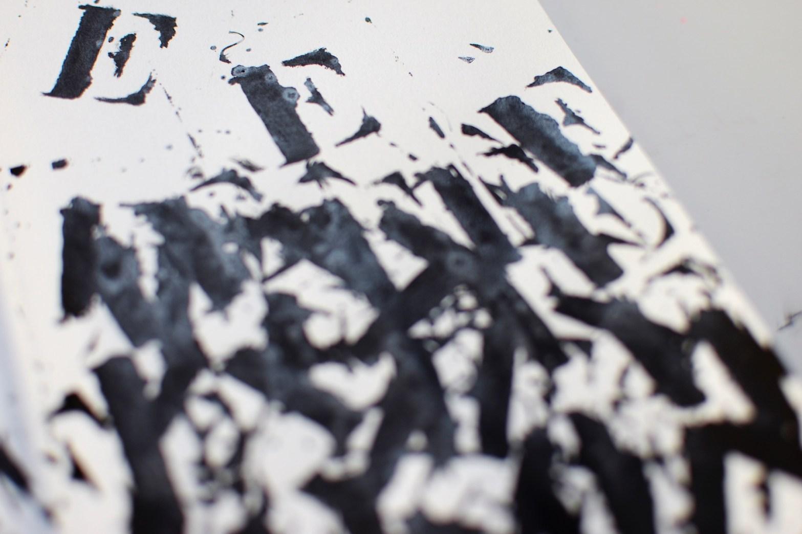 """Página de caderno com letra """"E"""" aplicada em estêncil"""