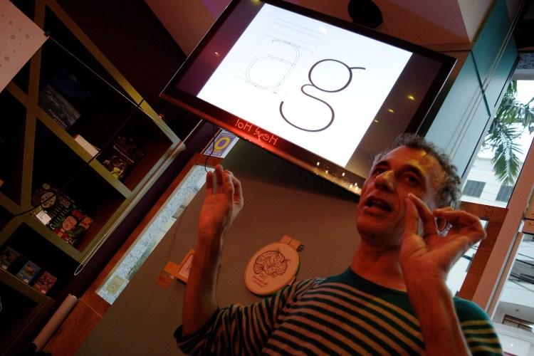 """Jefferson Cortinove fala em frente a uma tela de TV mostrando detalhes da letra """"g"""" no Coffee & Shop 18"""