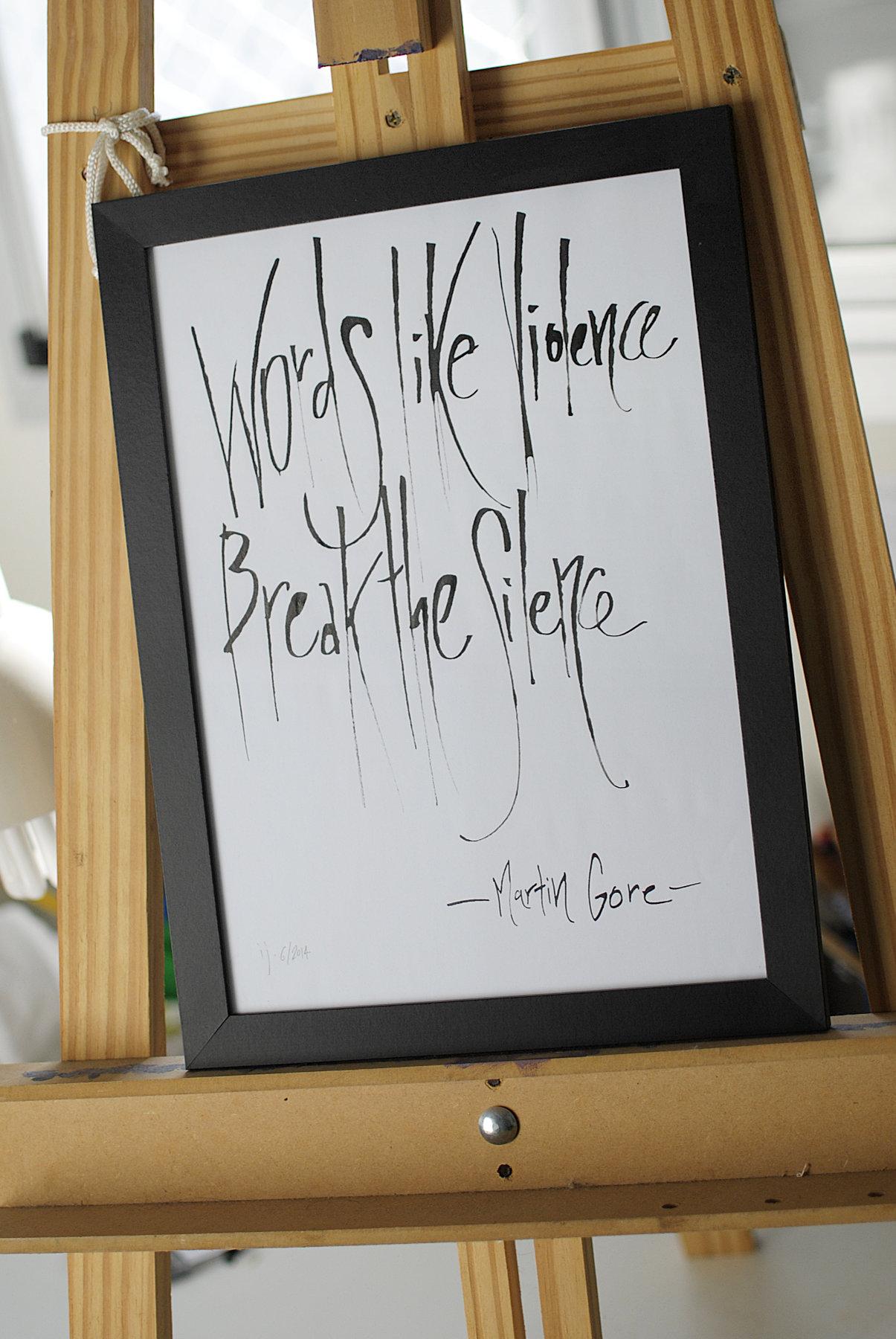 """Trabalho em caligrafia emoldurado, onde se lê """"Words like violence / Break the silence"""", apoiado em um cavalete"""
