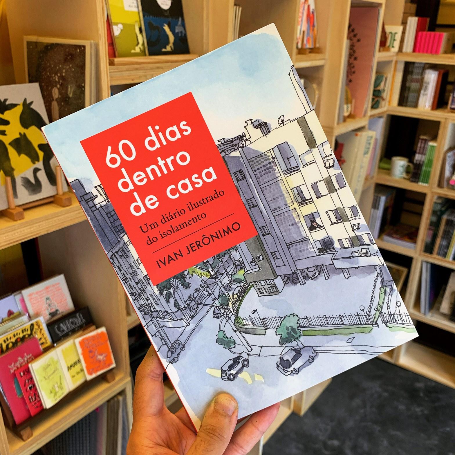 """Foto de mão segurando o livro """"60 dias dentro de casa – Um diário ilustrado do isolamento"""" entre as estantes no interior da Banca Curva"""