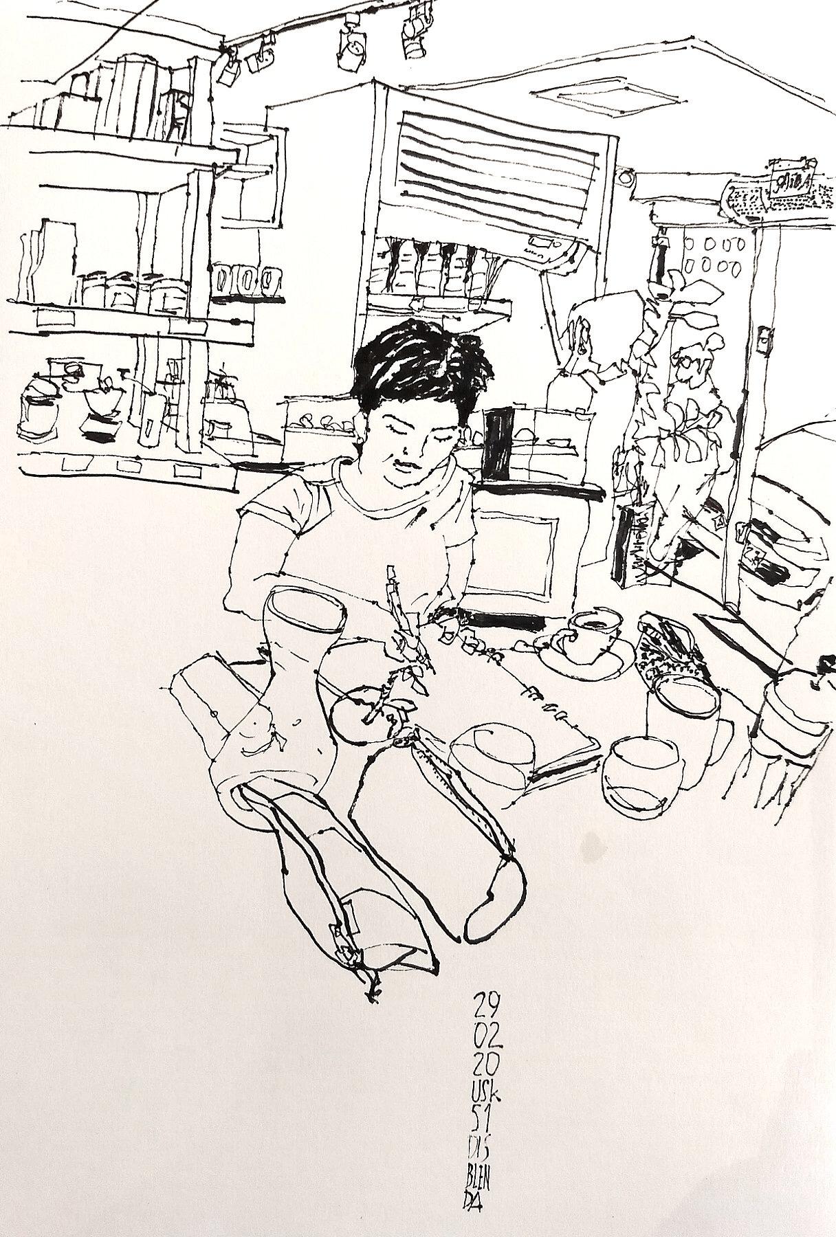 Desenho a traço retratando uma mulher desenhando em cima de uma mesa com cadernos e estojos. Ao fundo, o ambiente do café Disblenda