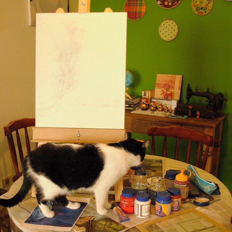 cavalete de mesa com tela já esboçada a lápis. Gata preto e branca caminha entre os potes de tinta