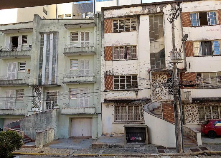 Foto dos dois prédios. O da esquerda é verde claro, enquanto o da direita é creme com detalhes em cerâmica vermelha. Ambos têm quatro pavimentos