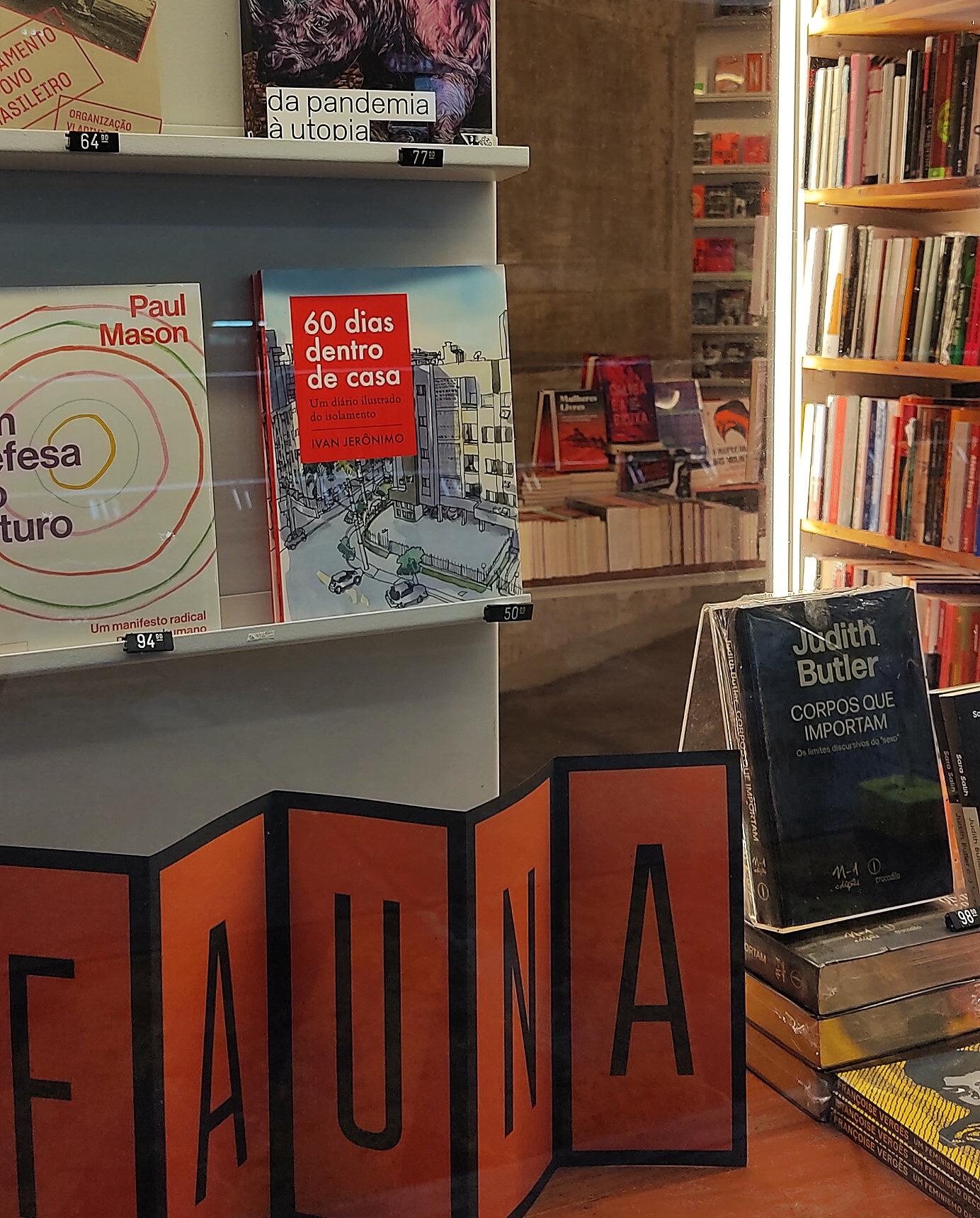 """Vitrine da livraria com livros expostos, dentre os quais o """"60 dias dentro de casa"""", de Ivan Jerônimo. Embaixo, em primeiro plano, nome da livraria em um display com dobras"""