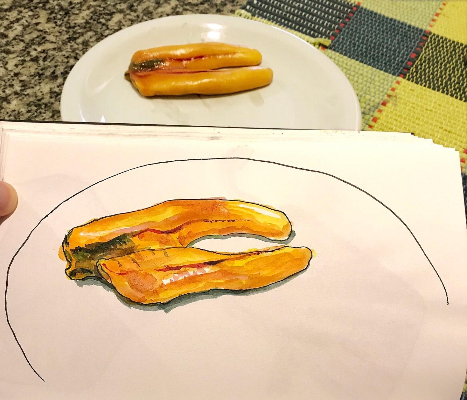 Página do caderno com desenho em aquarela de ovas de tainha. Ao fundo, prato com as ovas que autor usou como modelo