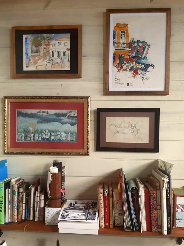 Parede com vários quadros, dentre eles o desenho da travessa. Embaixo, estante com livros