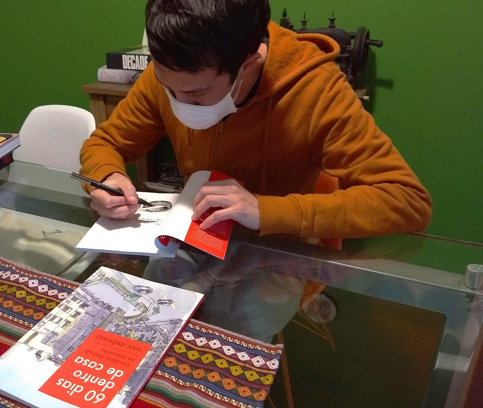 Autor de casaco ocre em uma mesa de vidro escrevendo a dedicatória em um livro aberto. À sua frente, outro livro fechado. Ao fundo, parede verde