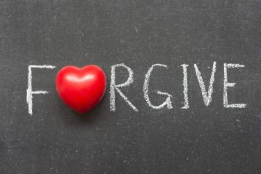 forgive word handwritten on chalkboard with heart symbol instead of O
