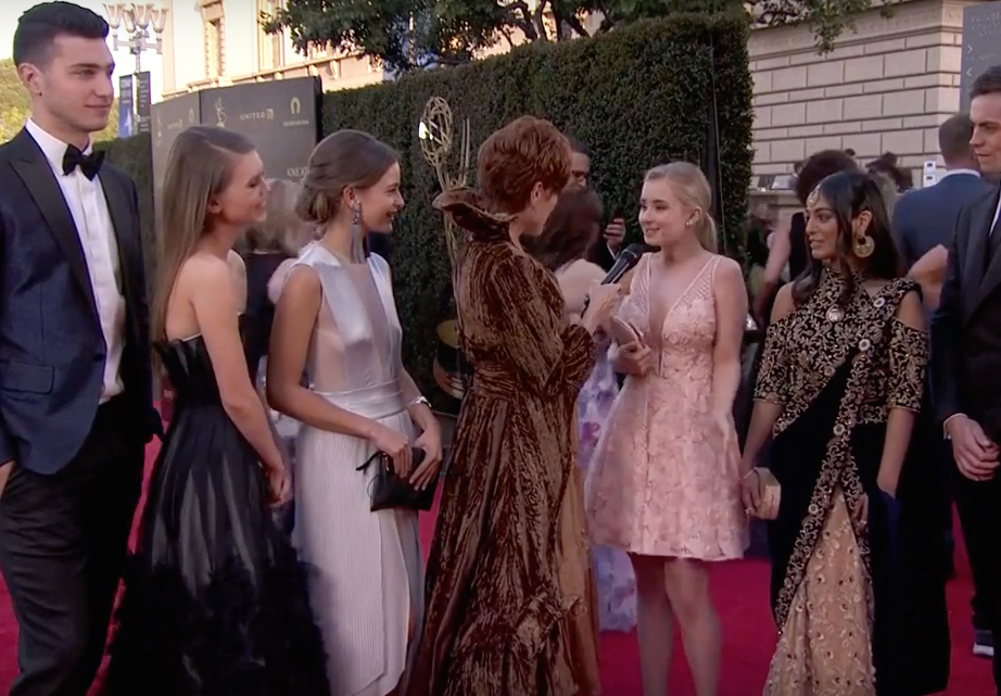 Carolyn Hennesy wears Ivey Abitz on the Emmys red carpet whilst interviewing cast from Free Rein on Netflix