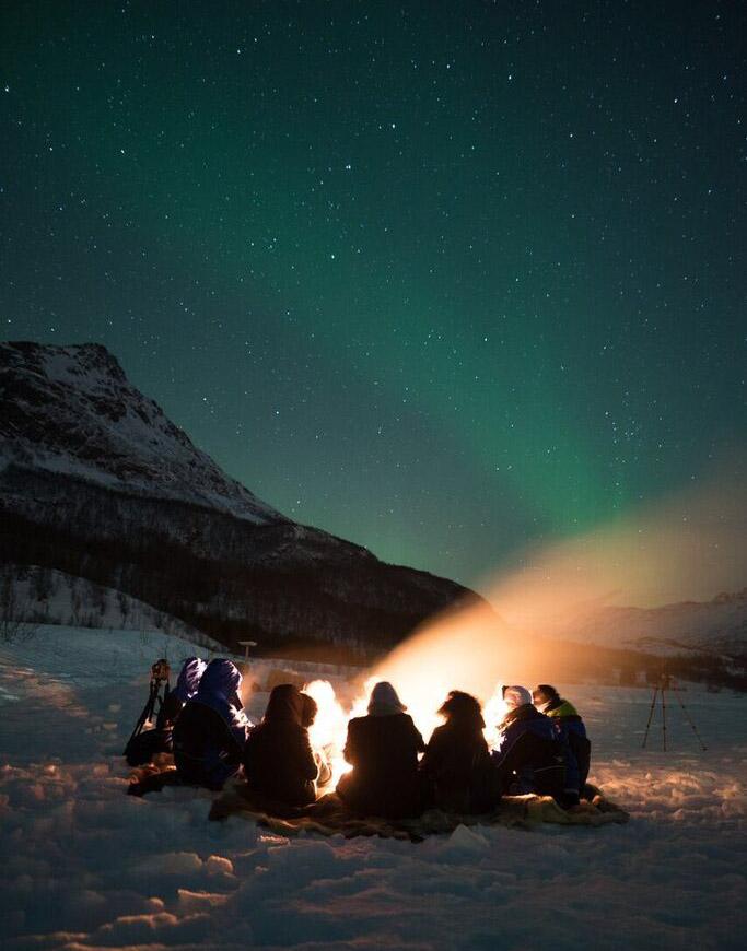 Fuoco sotto le stelle e una lieve aurora boreale.