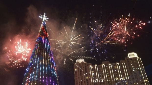 Fireworks explode next to a 38 metre Christmas tree on Christmas day at a shopping center in Jakarta on December 25, 2015. AFP PHOTO / ADEK BERRY